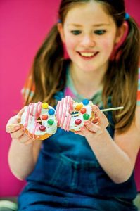 girl eating donutz on a stick